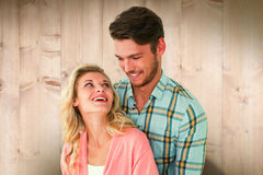 Composite image of attractive young couple embracing and smiling Stock Images