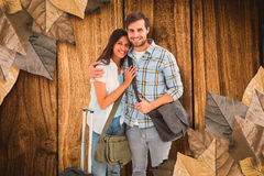 Composite image of attractive young couple going on their holidays Stock Image