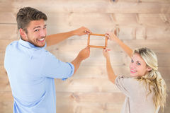 Composite image of attractive young couple hanging a frame Stock Photo