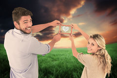 Composite image of attractive young couple hanging a frame Stock Images