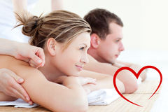 Composite image of attractive young couple having an acupunctre therapy Stock Images