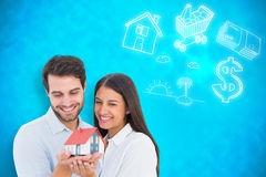 Composite image of attractive young couple holding a model house Stock Image