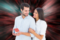 Composite image of attractive young couple holding a model house Royalty Free Stock Image