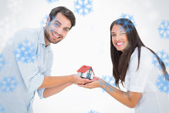 Composite image of attractive young couple holding a model house Stock Photo
