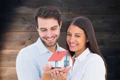 Composite image of attractive young couple holding a model house Royalty Free Stock Photo