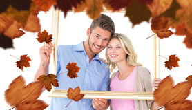 Composite image of attractive young couple holding picture frame Stock Photos