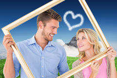 Composite image of attractive young couple holding picture frame Stock Images