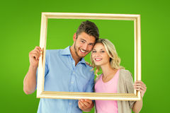 Composite image of attractive young couple holding picture frame Royalty Free Stock Image