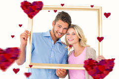 Composite image of attractive young couple holding picture frame. Attractive young couple holding picture frame against hearts stock photo