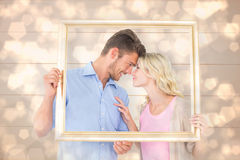 Composite image of attractive young couple holding picture frame Stock Photography