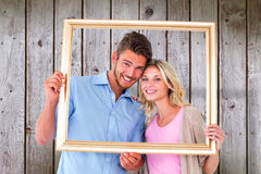Composite image of attractive young couple holding picture frame Stock Photo