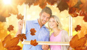 Composite image of attractive young couple holding picture frame Royalty Free Stock Photography
