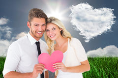 Composite image of attractive young couple holding pink heart Stock Images