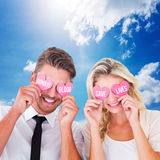 Composite image of attractive young couple holding pink hearts over eyes Stock Images