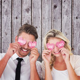 Composite image of attractive young couple holding pink hearts over eyes Stock Photos