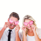 Composite image of attractive young couple holding pink hearts over eyes Royalty Free Stock Photography