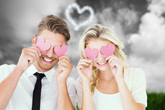 Composite image of attractive young couple holding pink hearts over eyes Stock Image