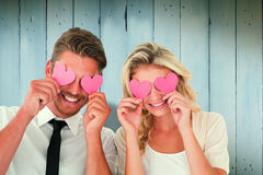 Composite image of attractive young couple holding pink hearts over eyes Royalty Free Stock Photos