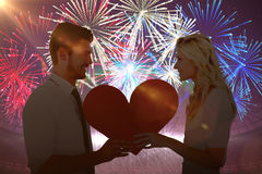 Composite image of attractive young couple holding red heart Stock Photo