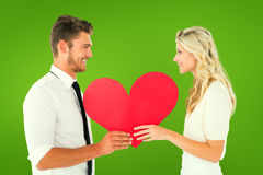 Composite image of attractive young couple holding red heart Stock Images