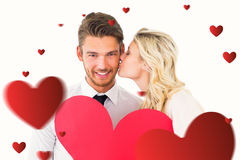 Composite image of attractive young couple holding red heart. Attractive young couple holding red heart against hearts royalty free stock photo