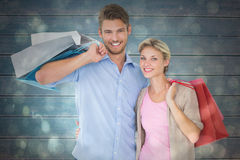 Composite image of attractive young couple holding shopping bags Royalty Free Stock Photo