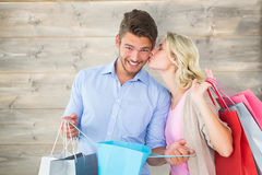 Composite image of attractive young couple holding shopping bags Stock Photos