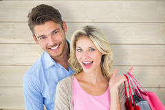 Composite image of attractive young couple holding shopping bags. Attractive young couple holding shopping bags against bleached wooden planks background Royalty Free Stock Photography