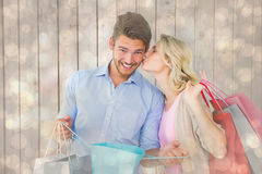 Composite image of attractive young couple holding shopping bags Stock Images