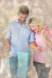Composite image of attractive young couple holding shopping bags Stock Image