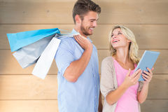 Composite image of attractive young couple holding shopping bags looking at tablet pc Royalty Free Stock Images