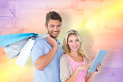 Composite image of attractive young couple holding shopping bags using tablet pc Royalty Free Stock Photography