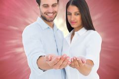 Composite image of attractive young couple holding their hands out Stock Photo