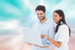 Composite image of attractive young couple holding their laptop Royalty Free Stock Photography