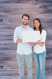 Composite image of attractive young couple holding their laptop Royalty Free Stock Images