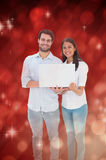 Composite image of attractive young couple holding their laptop Stock Photography