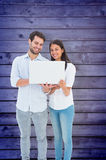Composite image of attractive young couple holding their laptop Royalty Free Stock Photos