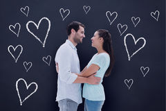 Composite image of attractive young couple hugging each other Stock Photos