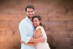 Composite image of attractive young couple hugging and smiling at camera Stock Photos