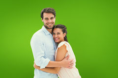 Composite image of attractive young couple hugging and smiling at camera Royalty Free Stock Photos