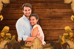 Composite image of attractive young couple hugging and smiling at camera. Attractive young couple hugging and smiling at camera against overhead of wooden planks Royalty Free Stock Photos