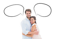 Composite image of attractive young couple hugging and smiling at camera. Attractive young couple hugging and smiling at camera against speech bubble Royalty Free Stock Image