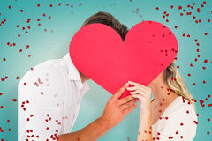 Composite image of attractive young couple kissing behind large heart. Attractive young couple kissing behind large heart against blue vignette background stock photo