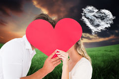 Composite image of attractive young couple kissing behind large heart Royalty Free Stock Images