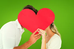 Composite image of attractive young couple kissing behind large heart Royalty Free Stock Image