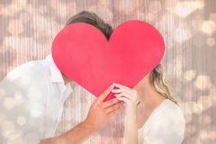 Composite image of attractive young couple kissing behind large heart Stock Photography