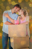 Composite image of attractive young couple leaning on boxes with piggy bank Stock Photos