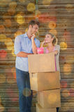 Composite image of attractive young couple leaning on boxes with piggy bank Royalty Free Stock Images
