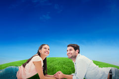 Composite image of attractive young couple looking up Royalty Free Stock Images