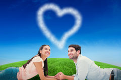 Composite image of attractive young couple looking up Royalty Free Stock Image